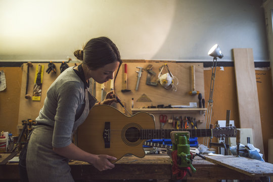 woman luthier is repairing a guitar in her musical instrument workshop