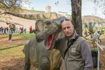 Belgrade, Serbia - October 05, 2014: Man hugging dinosaurs in the dino park, Belgrade, Serbia: