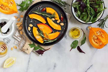 Roasted pumpkin salad with fresh herbs and lemon dressing overhead a white marble board.