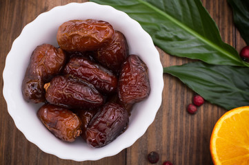 Dried dates exotic fruit on a plate in a rustic style. Wooden background. Top view. Close-up