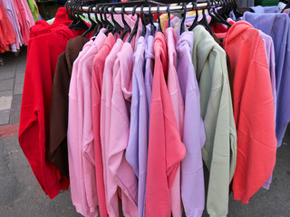 colorful sweatshirts for sale at an outdoor market