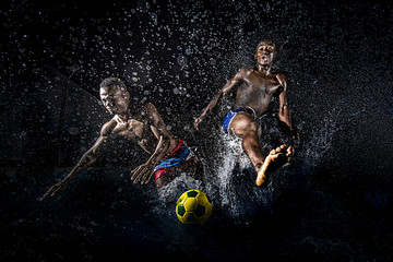 Black men playing soccer over a black background