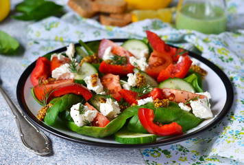 Vegetable salad with tomatoes, spinach and feta cheese on a concrete background.
