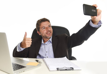 businessman in suit working at office laptop computer desk using mobile phone for taking selfie photo