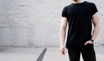 Young muscular bearded man wearing black tshirt and jeans posing outside. White bricks wall on the background. Hotizontal mockup, front view