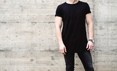 Young muscular man wearing black tshirt and jeans posing in center of modern city. Empty concrete wall on the background. Hotizontal mockup.