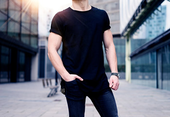 Young caucasian muscular man wearing black tshirt and jeans posing on the street of the modern city. Blurred background. Hotizontal mockup.