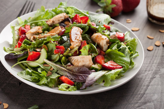 Strawberry Orange Honey Balsamic Salad on spring baby greens and spinach on a dark wooden background