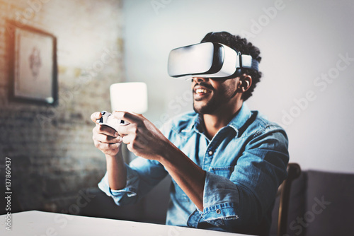 2deef9450fb African man enjoying virtual reality glasses while relaxing in living  room.Happy young guy with VR headset playing video game at home.Blurred.