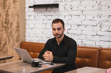 Portrait of handsome young man with laptop at cafe looking to camera