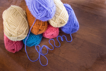 """Eight skeins of pink, cream, gold, turquoise and lavender yarn at an angle from above on wooden table. Lavender yarn spells the work """"yarn"""" in cursive."""