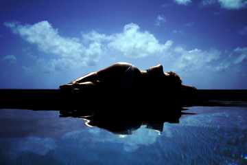 silhouette of beautiful woman in bikini reflected in swimming pool
