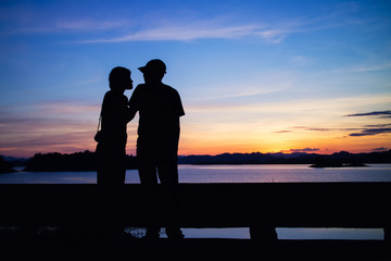 Silhouette of lovely couple on lake