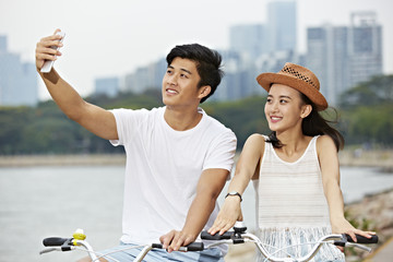 young asian couple riding bike and taking a selfie
