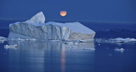 Full moon over an iceberg at dusk, Saqqaq, Disko Bay, Greenland, September 2009