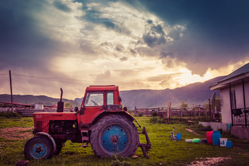 Very old tractor on the grass field and dramatic sky