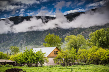 House near the mountains and beautiful cloudy sky, Kazakhstan