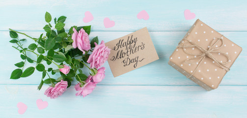 Pink roses with paper greeting card and gift box for Mothers day
