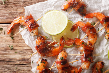Grilled shrimp with bacon, thyme and lime close up on the table. horizontal top view