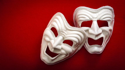 Comedy and Tragedy theatrical mask isolated on a red background and copy space