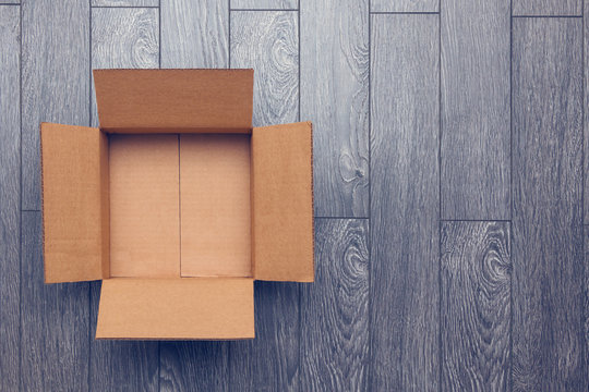 Empty open box on wooden surface with empty space