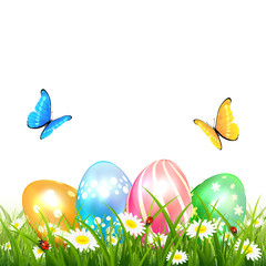 Butterflies flying over colored Easter eggs on grass
