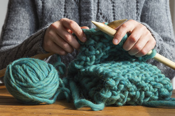Woman knitting green woolen scarf