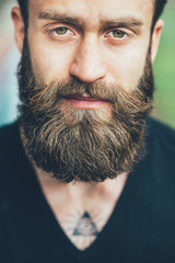 Portrait young bearded man loooking camera serious
