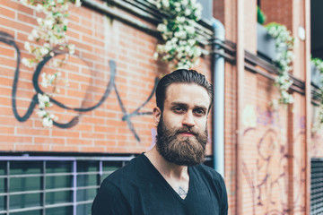 Young bearded tattooed man portrait overlooking