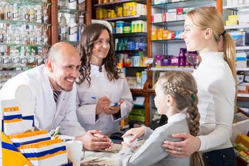 Two pharmacists helping customers