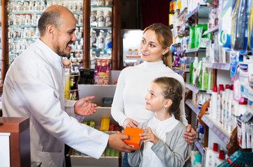 Mature pharmacist consulting customers