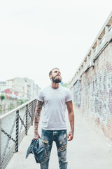 Young bearded tattooed man looking up pensive