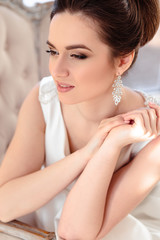 close-up portrait of beautiful brunette bride with elegant hairstyle and makeup wearing long luxury wedding dress