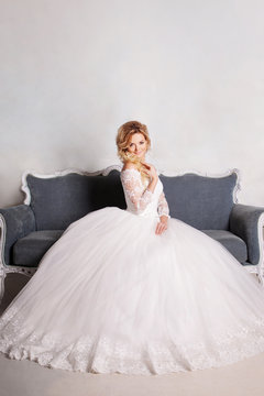 Portrait of charming woman in wedding dress. The girl bride sits in a chair