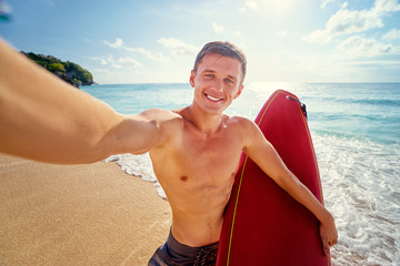 Hobby and vacation. Portrait of surfer. Young man taking selfie on the sea beach.