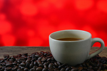 Coffee cup and coffee beans on table with red background
