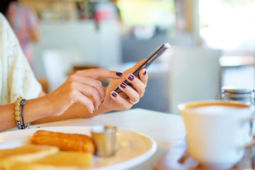Woman holding mobile phone in hands, texting in social media. Breakfast of business lady.