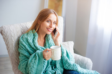 woman with cup of tea talking by smart phone