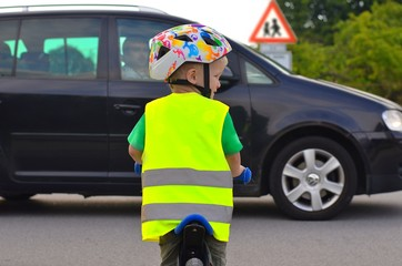 Little boy riding a bike and wearing reflective vest and helmet on the road. Driving car in front of him.