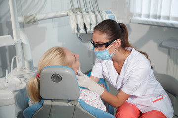 Female dentist examining a patient in the dental office for a woman