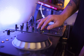 close up of a music technician mixing tracks on his studio