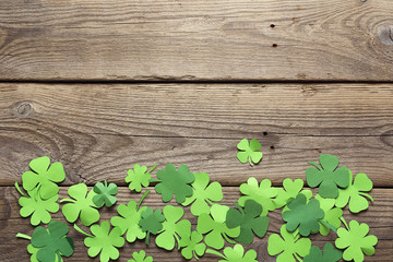 Paper clover leaves on the old wooden background. Lucky shamrock. Space for text.