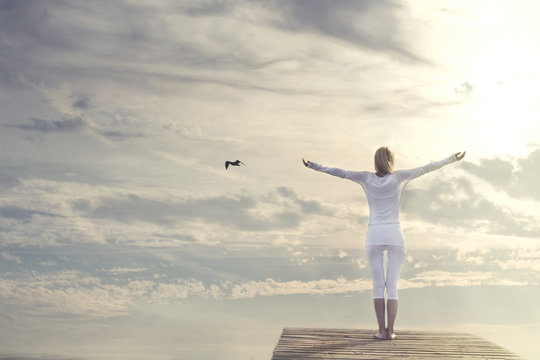 woman with open arms meditating in front of a spectacular sky