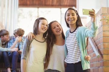 Smiling schoolgirls taking selfie with mobile phone in corridor