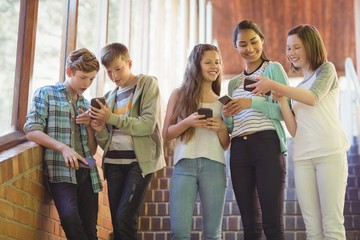 Group of smiling school friends using mobile phone in corridor