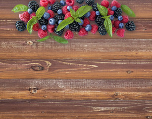 Various fresh summer berries on wooden background. Ripe blueberries, raspberries and blackberries. Berries at border of image with copy space for text.