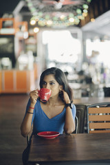 young indian woman having coffee in a cafe