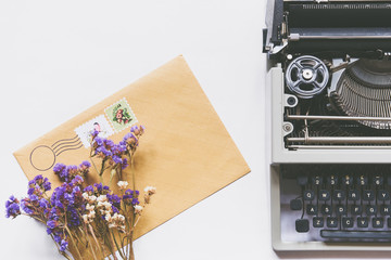 Top view of dry flowers, typewriter and mail envelope