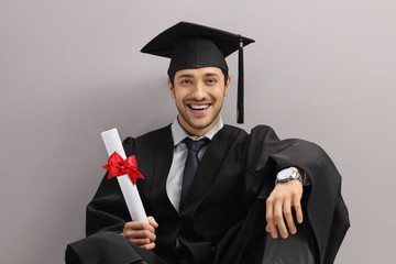 Happy graduate student with diploma leaning against gray wall