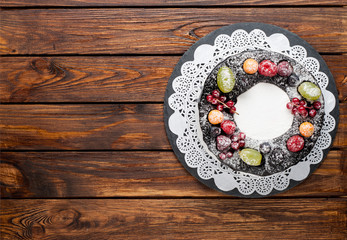 chocolate berry cake on plate over brown wooden background